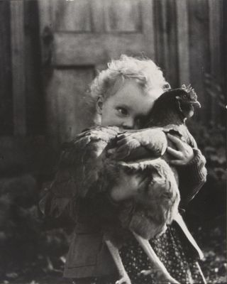 Girl (Nell Dorr) hugging chicken