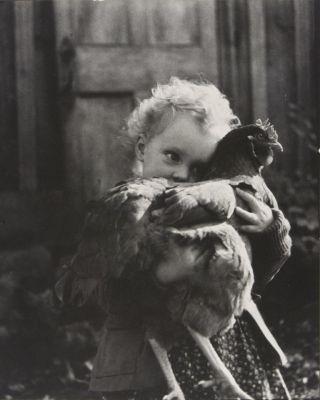 Girl (Nell Dorr) hugging chicken